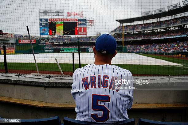 A fan in a David Wright jersey waits during a rain delay for the start of a game between the New York Mets and the Washington Nationals at Nationals...