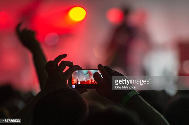 A fan in the crowd taking a photograph with a mobile phone as the Manic Street Preachers perform during a date of the bands 2014 UK Tour at De...