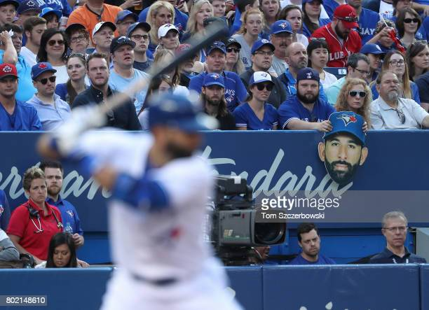 A fan in the front row holds a cardboard cutout of the head of Jose Bautista of the Toronto Blue Jays as he bats in the first inning during MLB game...