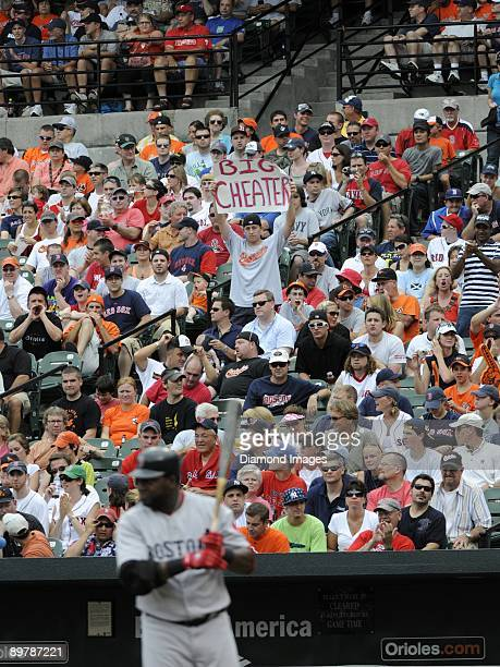 A fan in the seats along the firstbase line stands up with a sign reading Big Cheater as designatedhitter David Ortiz of the Boston Red Sox steps...
