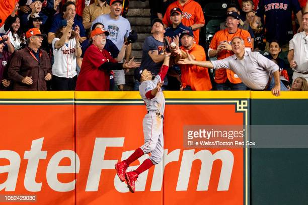 A fan interferes with Mookie Betts of the Boston Red Sox as he attempts to catch a ball hit by Jose Altuve of the Houston Astros in the first inning...