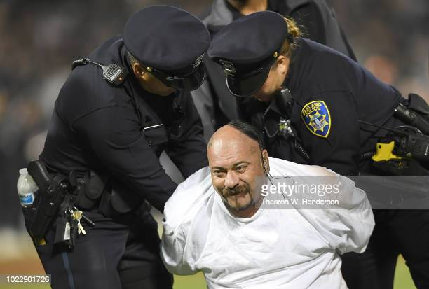 A fan is apprehended and put into handcuffs by Oakland police officers running onto the field during an NFL preseason football game between the Green...