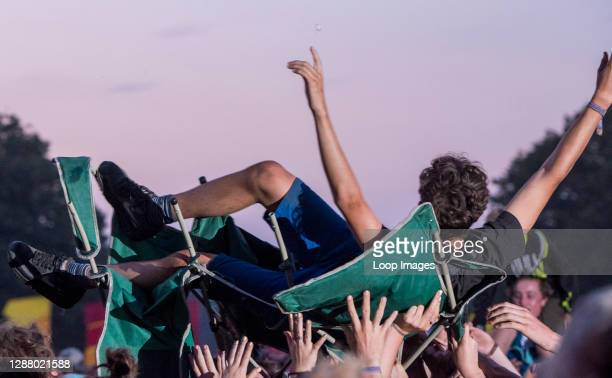 Fan is crowd surfing in his deck chair during Alt J performance at Latitude Festival 2018.