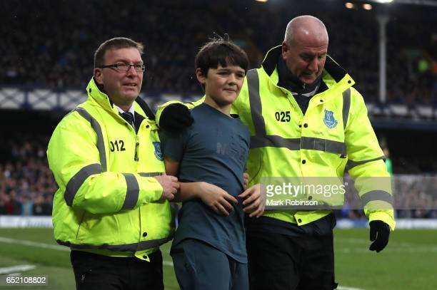 A fan is escorted away after he runs on the pitch to celebrate after Everton's third goal during the Premier League match between Everton and West...