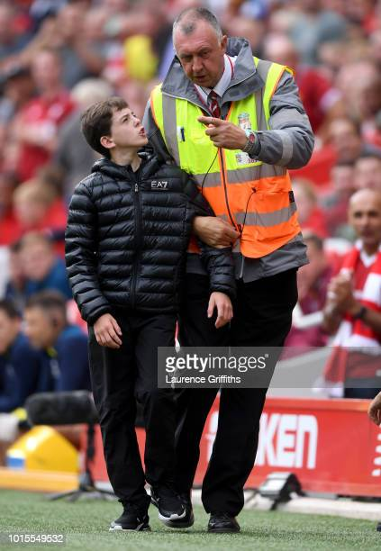 A fan is escorted off the pitch after running onto the pitch during the Premier League match between Liverpool FC and West Ham United at Anfield on...