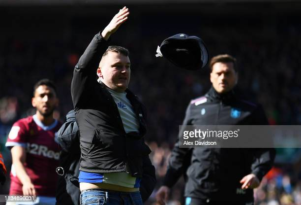 A fan is escorted off the pitch after striking Jack Grealish of Aston Villa during the Sky Bet Championship match between Birmingham City and Aston...