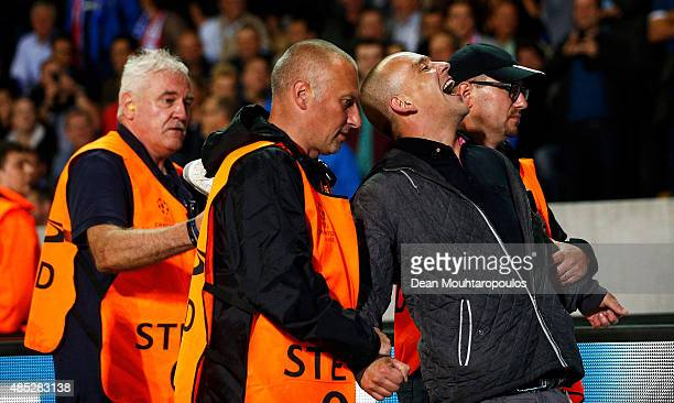 A fan is led away by stewards during the UEFA Champions League qualifying round play off 2nd leg match between Club Brugge and Manchester United held...