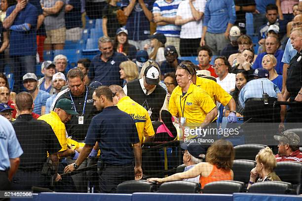 A fan is removed from the stands on a backboard by medics after being hit with a foul ball tipped by Steven Souza Jr #20 of the Tampa Bay Rays during...