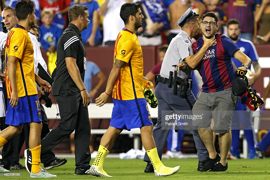 A fan is restrained by a police officer after he ran onto the field and neared Luis Suarez #9 of Barcelona following their loss to Chelsea during the International Champions Cup North America at FedExField on July 28, 2015 in Landover, Maryland. Chelsea won in a penalty shootout.