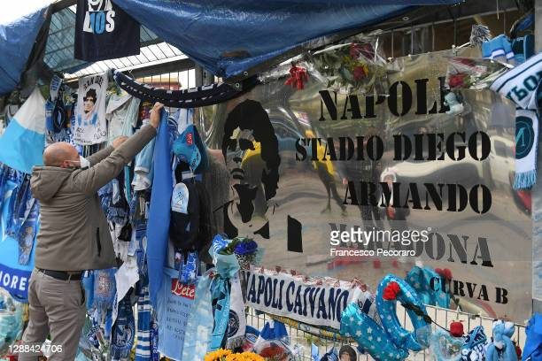 Fan is seen placing tributes to the deceased Diego Maradona outside the stadium prior to the Serie A match between SSC Napoli and AS Roma at Stadio...