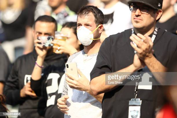 Fan is seen wearing a face mask in the stands due to smoke from a forest fire in Butte County at the NFL game between the Oakland Raiders and the Los...
