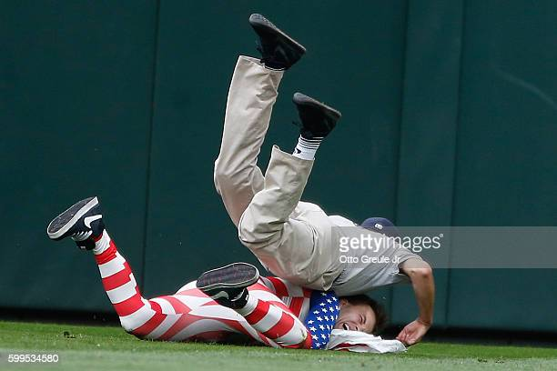 A fan is tackled by security after running onto the field in the ninth inning of the game between the Seattle Mariners and the Texas Rangers at...