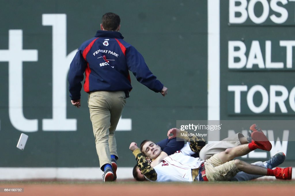 A fan is tackled by security after rushing the field during the eighth inning of the opening day game between the Boston Red Sox and the Pittsburgh Pirates at Fenway Park on April 3, 2017 in Boston, Massachusetts.