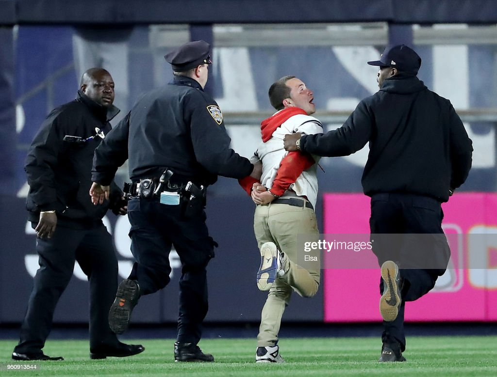 A fan is taken off the field by security after he ran onto the field in seventh inning during the game between the New York Yankees and the Minnesota Twins at Yankee Stadium on April 24, 2018 in the Bronx borough of New York City.