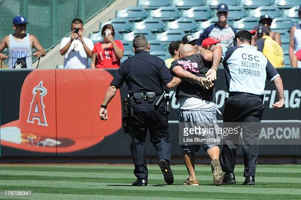 A fan is taken off the field by security during the game between the Los Angeles Angels of Anaheim and the Minnesota Twins at Angel Stadium of...