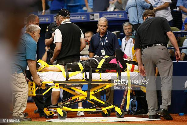 A fan is wheeled through the field on a stretcher by medics after being hit in the stands with a foul ball tipped by Steven Souza Jr #20 of the Tampa...
