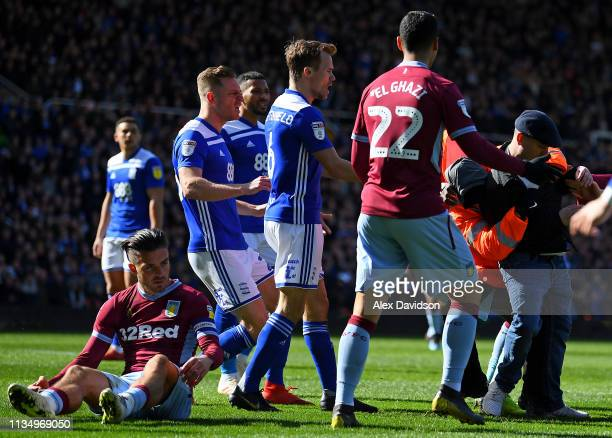 A fan is wrestled to the ground by a steward after punching Jack Grealish of Aston Villa during the Sky Bet Championship match between Birmingham...