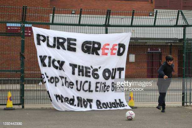 Fan kicks a ball in front of a banner reacting to the collapse of the planned creation of a European Super League, ahead of the English Premier...