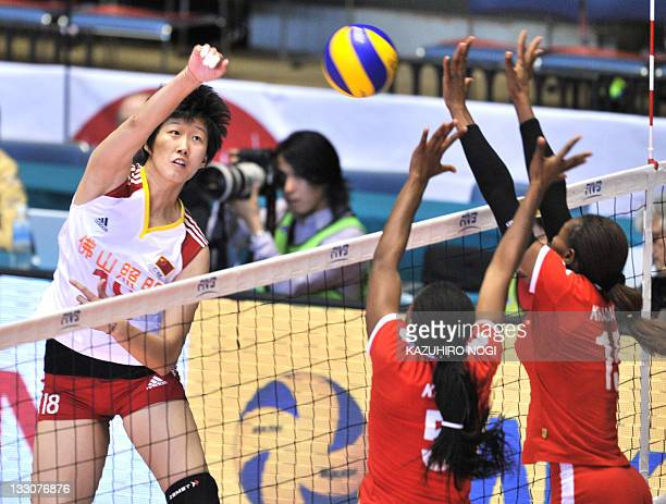 Fan Linlin of China spikes over Kenyan players Diana Khisa and Brackcides Khadambi during a match of the World Cup women's volleyball tournament in...