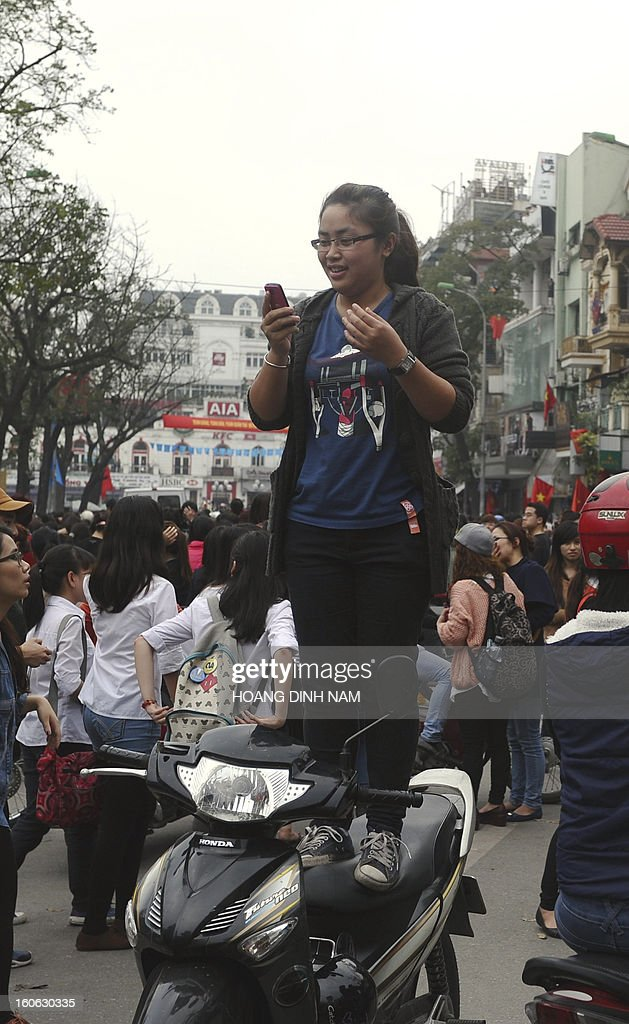 A fan looks at her phone after a van carrying unidentified South Korean stars arrived to film a popular reality TV show 'Running Man'in downtown Hanoi on February 4, 2013. Stars including Song Ji Hyo, Hye Jin, Haha, Jong Kook, Lee Dong Wooka were amongst the personalities to attend the filming. AFP PHOTO/HOANG DINH Nam
