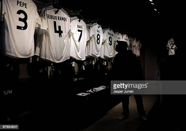 A fan looks at shirt of Real Madrid star players on the day after Real Madrid's UEFA Champions League aggregate defeat against Lyon at the Estadio...