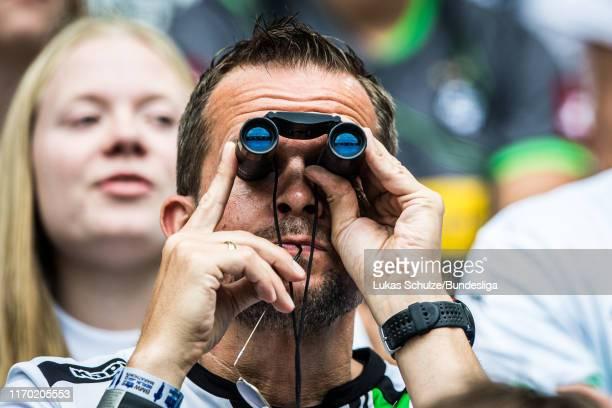 Fan looks through a binoculars during the Bundesliga match between Borussia Mönchengladbach and Fortuna Düsseldorf at Borussia-Park on September 22,...