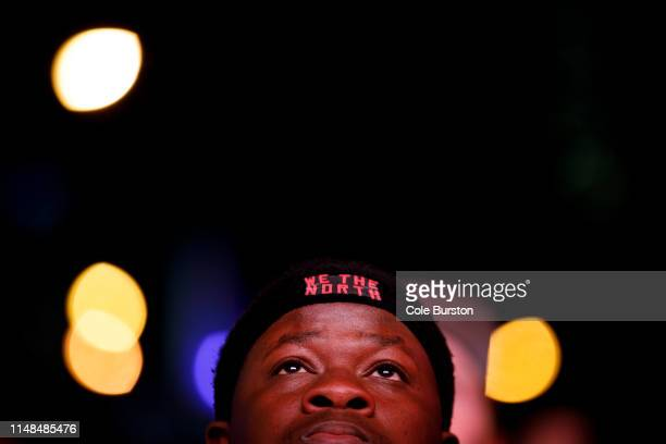 A fan looks up at a screen as he alongside other Toronto Raptors fans gather to watch Game 4 of the NBA Finals series outside Scotiabank Arena at...