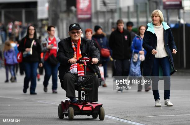 A fan makes his way to the stadium prior to the Premier League match between Arsenal and Swansea City at Emirates Stadium on October 28 2017 in...
