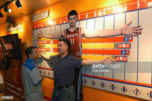 A fan measures his arm span against a chart featuring Yao Ming of the Houston Rockets during AllStar NBA Jam Session at the Los Angeles Convention...
