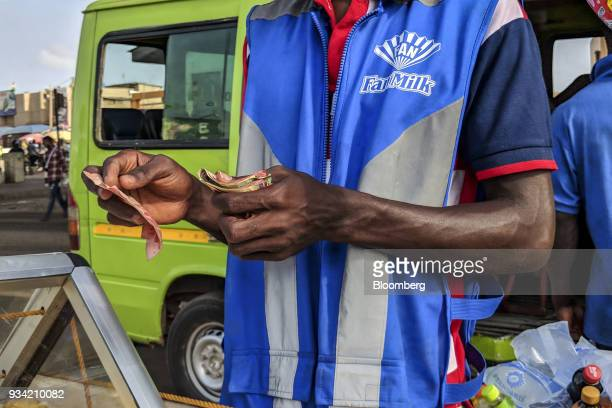 A Fan Milk Plc ice cream and frozen dairy products vendor counts Ghana cedi banknotes in Accra Ghana on Thursday March 15 2018 Ghana wants to shake...