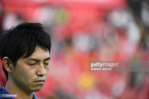 A fan observes a moment of silence for victims of typhoon Hagibis before the start of the Japan 2019 Rugby World Cup Pool D match between Wales and...