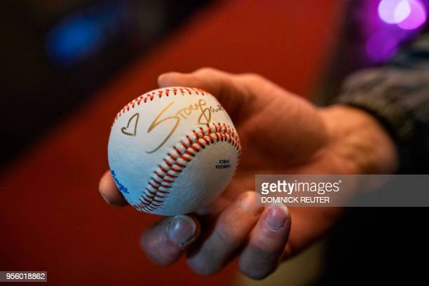 Fan of adult film star Stephanie Clifford, AKA Stormy Daniels, shows off a baseball autographed by the star outside the Penthouse Club in...