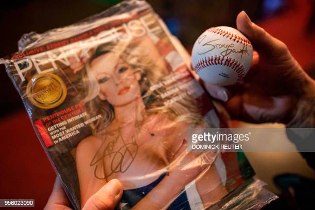 Fan of adult film star Stephanie Clifford, AKA Stormy Daniels, shows off a magazine and baseball autographed by the star outside the Penthouse Club...
