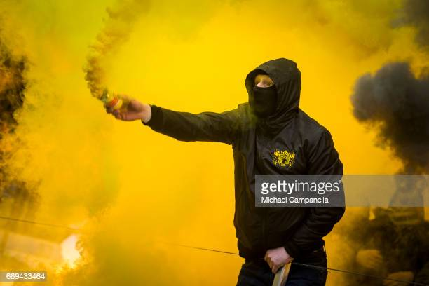 A fan of AIK lights a smoke bomb during an Allsvenskan match between AIK and Hammarby IF at Friends arena on April 17 2017 in Solna Sweden