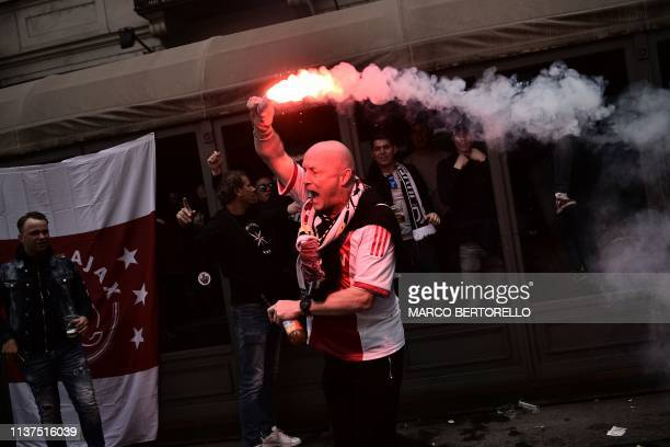 Fan of Ajax holds a flare and cheers as Ajax fans gather in a pub in downtown Turin prior to the UEFA Champions League quarter-final second leg...