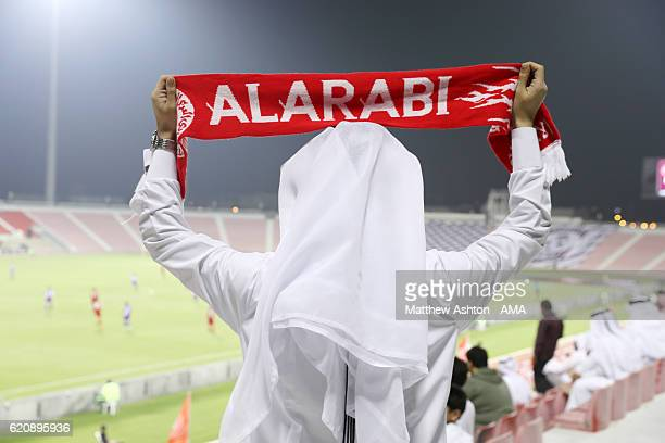 A fan of Al Arabi holds up his scarf during the game in the Grand Hamad Stadium during the Al Arabi v Muaither SC match in the Qatar Stars League at...