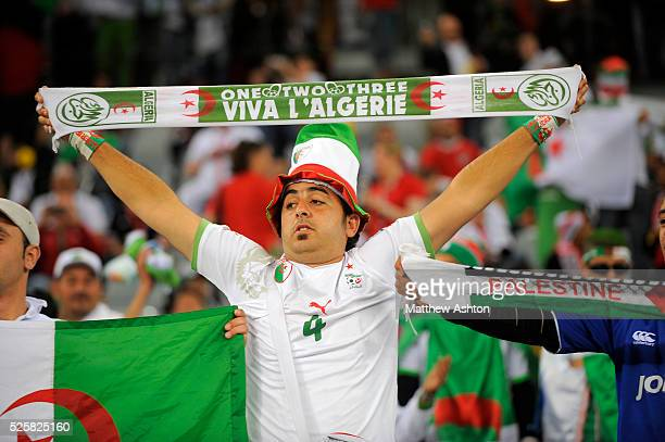 A fan of Algeria holding up a scarf