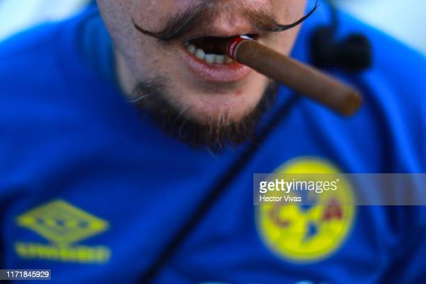 Fan of America poses with a cigar the 12th round match between America and Chivas as part of the Torneo Apertura 2019 Liga MX at Azteca Stadium on...