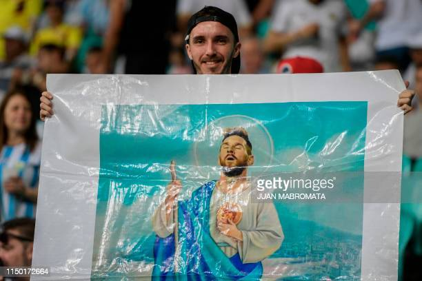 A fan of Argentina displays a religious image with the face of striker Lionel Messi before the start of the Copa America football tournament group...