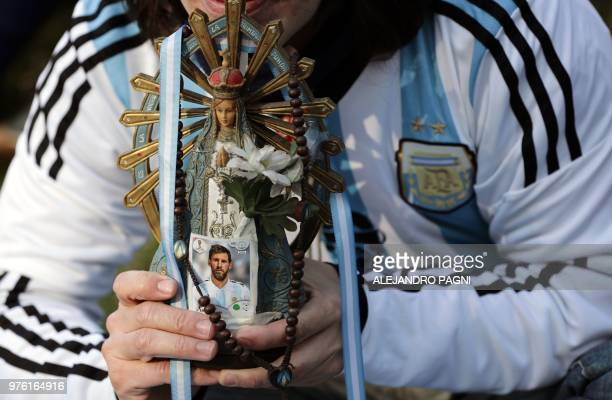 TOPSHOT A fan of Argentina holds an image of the Virgen del Lujan bearing a picture of Lionel Messi while watching the FIFA World Cup Russia 2018...