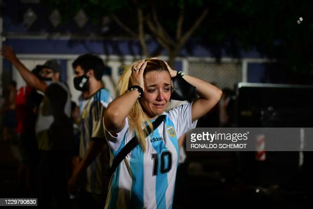 Fan of Argentinian football legend Diego Maradona cries as she gathers with other fans to pay homage on the day of his death at Argentinos Junior's...