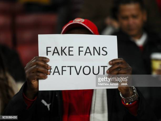 A fan of Arsenal holds up a sign which reads Fake Fans Out during UEFA Europa League Round of 32 match between Arsenal and Ostersunds FK at the...