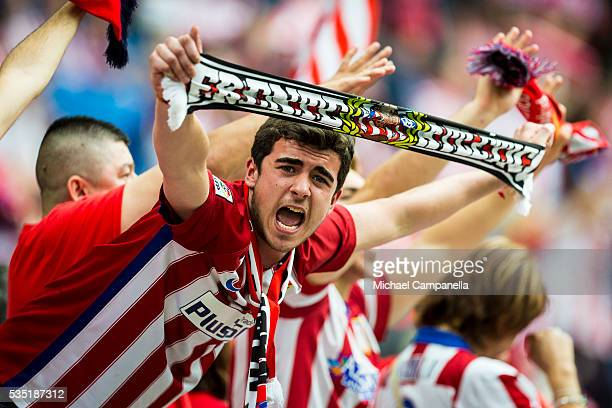 A fan of Atletico Madrid holds a scarf showing his support during the UEFA Champions League final between Real Madrid and and Club Atletico Madrid at...