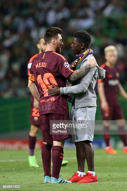 A fan of Barcelona's Argentine forward Lionel Messi enters the field to hug him during the UEFA Champions League football match Sporting vs Barcelona...