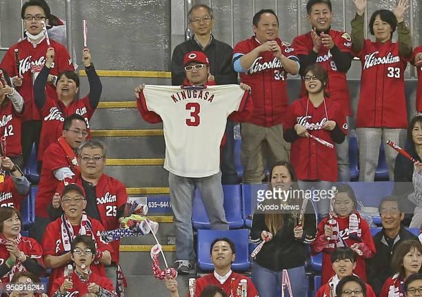A fan of baseball legend Sachio Kinugasa shows off a replica of his Hiroshima Carp uniform during a game between the team and the DeNA BayStars at...