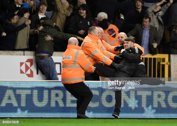 A fan of Birmingham City is dragged from the pitch during the Sky Bet Championship match between Wolverhampton Wanderers and Birmingham City at...