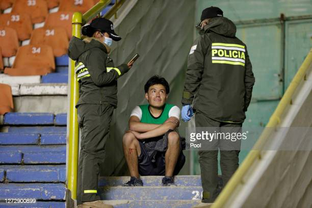 Fan of Bolivar who managed to get into the stadium speaks to police officers during a group B match of Copa CONMEBOL Libertadores 2020 between...