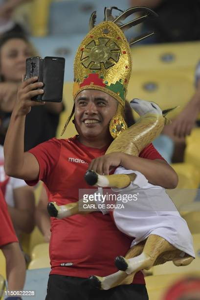 A fan of Bolivia takes a selfie with a llama with a Peruvian jersey during the Copa America football tournament group match between Bolivia and Peru...