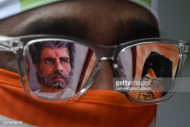 Fan of Bollywood actor Amitabh Bachchan waits to participate in a special prayer organised for his recovery after testing positive for COVID-19...