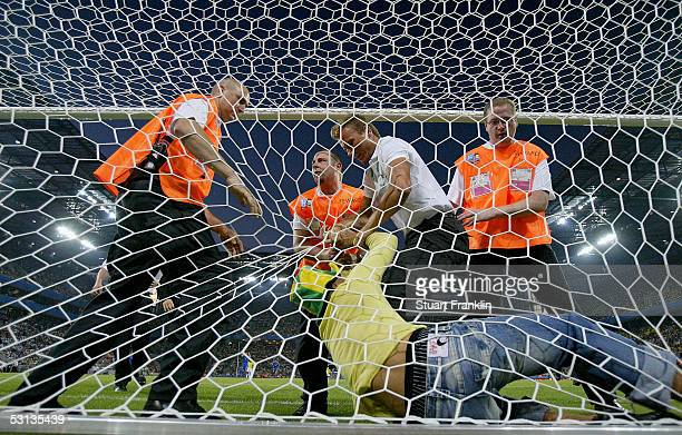A fan of Brazil who invaded the pitch is escorted out of the net by stewards during the FIFA Confederations Cup match between Japan and Brazil at...